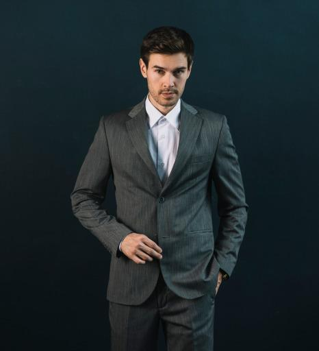confident-young-man-with-his-hand-pocket-against-black-background 1